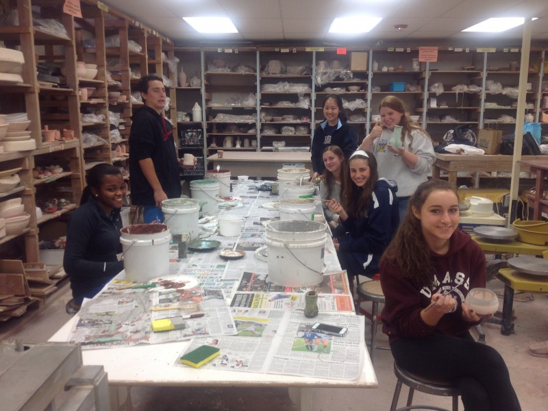At a workshop on raku firing techniques, Upper School students in the Alternative Ceramic Techniques class prepared their pieces for the initial firing step.
